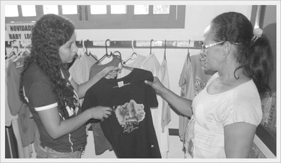Edilene, na lojinha, mostrando uma blusa alusiva ao Santuário do Caraça.