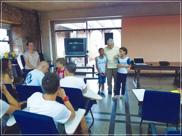 Padre Lauro Palú ajudando (traduzindo) os meninos a explicarem o trabalho deles na escola para os estudantes da Itália.